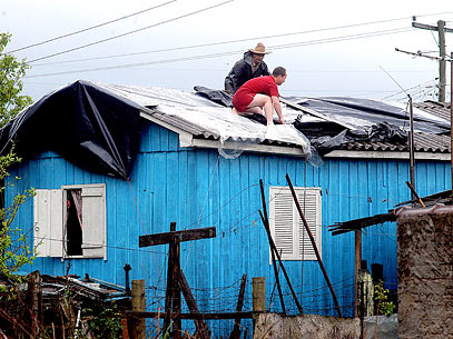 Moradores cobrem telhado de casa que foi danificado por chuva de granizo, em Santa Cruz do Sul. Foto: Lula Helfer/Gazeta do Sul/Divulgação